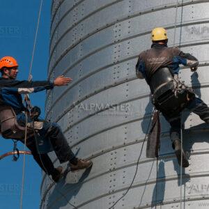 Алпинисти работят по външната страна на метален силоз