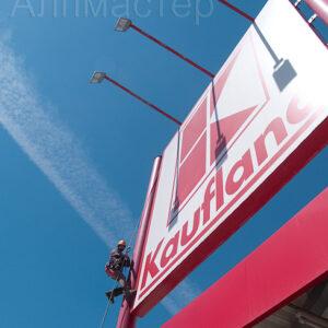Алпинист боядисва пилоните на рекламното съоръжение Kaufland
