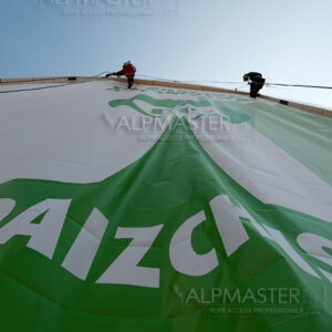 Алпинисти монтират  рекламна визия, отпечатана върху винил