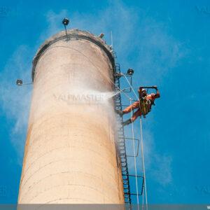 Почистване на бетонната повърхност на комин, като подготовка за нанасяне на боя и сигнална маркировка
